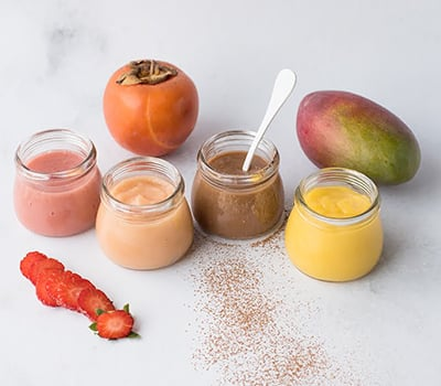 frascos de iogurte coloridos ladeados por morangos cortados às rodelas, um diospiro e uma manga inteira